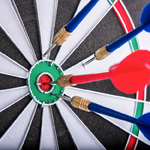 A Dart Board With 3 Blue Darts And 1 Red Dart In the Bullseye