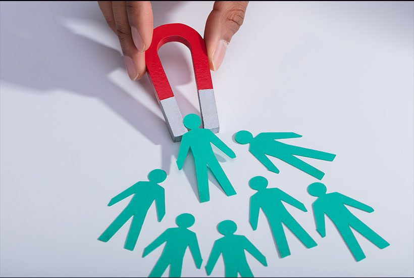 Miniature Magnet Attracting A Bunch of Paper Cutout People