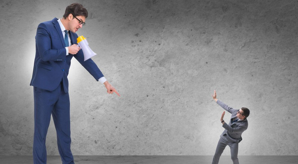 Businessman With A Loudhailer Yelling And Pointing At A Smaller Businessman
